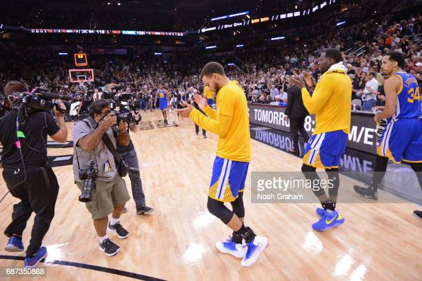 Stephen Curry of the Golden State Warriors claps and walks off the court after winning Game Four of the Western Conference Finals against the San...