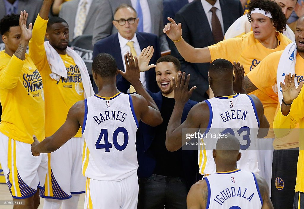 Stephen Curry of the Golden State Warriors congratulates Harrison Barnes and Draymond Green during a time out of their game against the Portland...