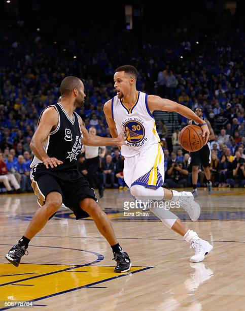 Stephen Curry of the Golden State Warriors dribbles around his back while covered by Tony Parker of the San Antonio Spurs at ORACLE Arena on January...