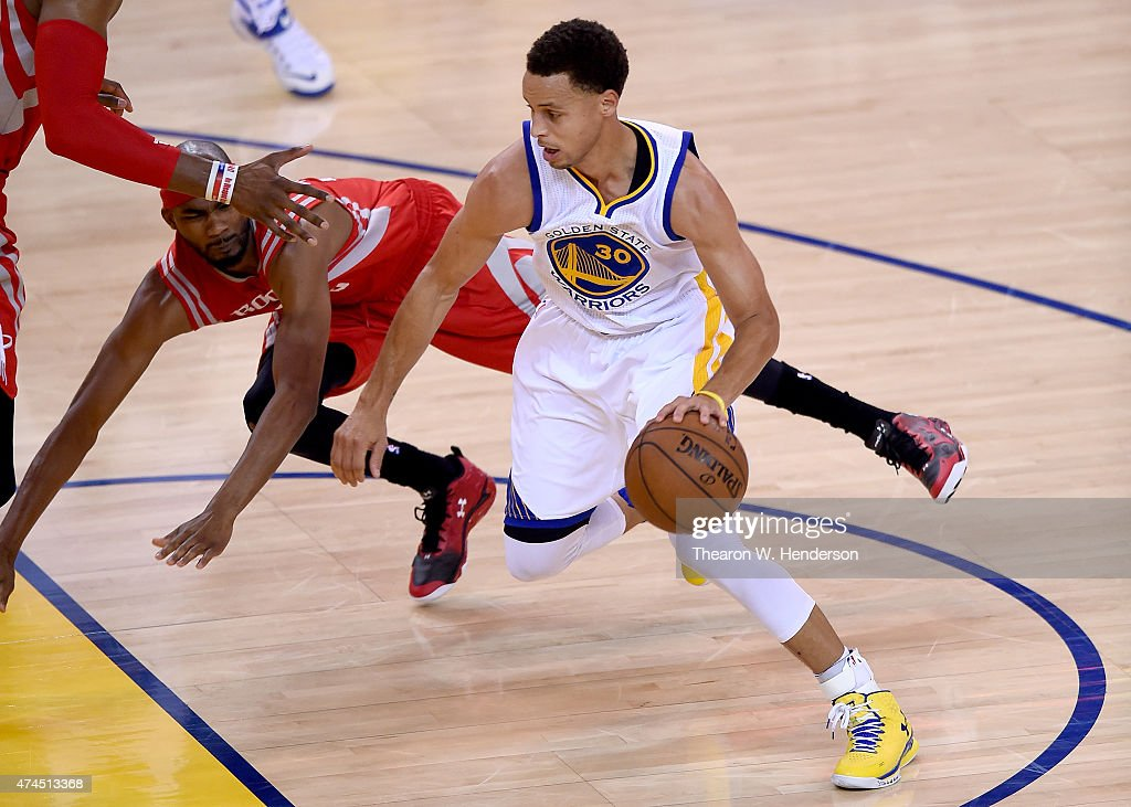 Stephen Curry of the Golden State Warriors dribbles past Corey Brewer of the Houston Rockets during the first half in Game Two of the Western...