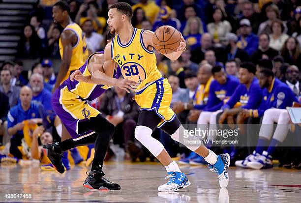 Stephen Curry of the Golden State Warriors dribbles past Jordan Clarkson of the Los Angeles Lakers during their NBA basketball game at ORACLE Arena...