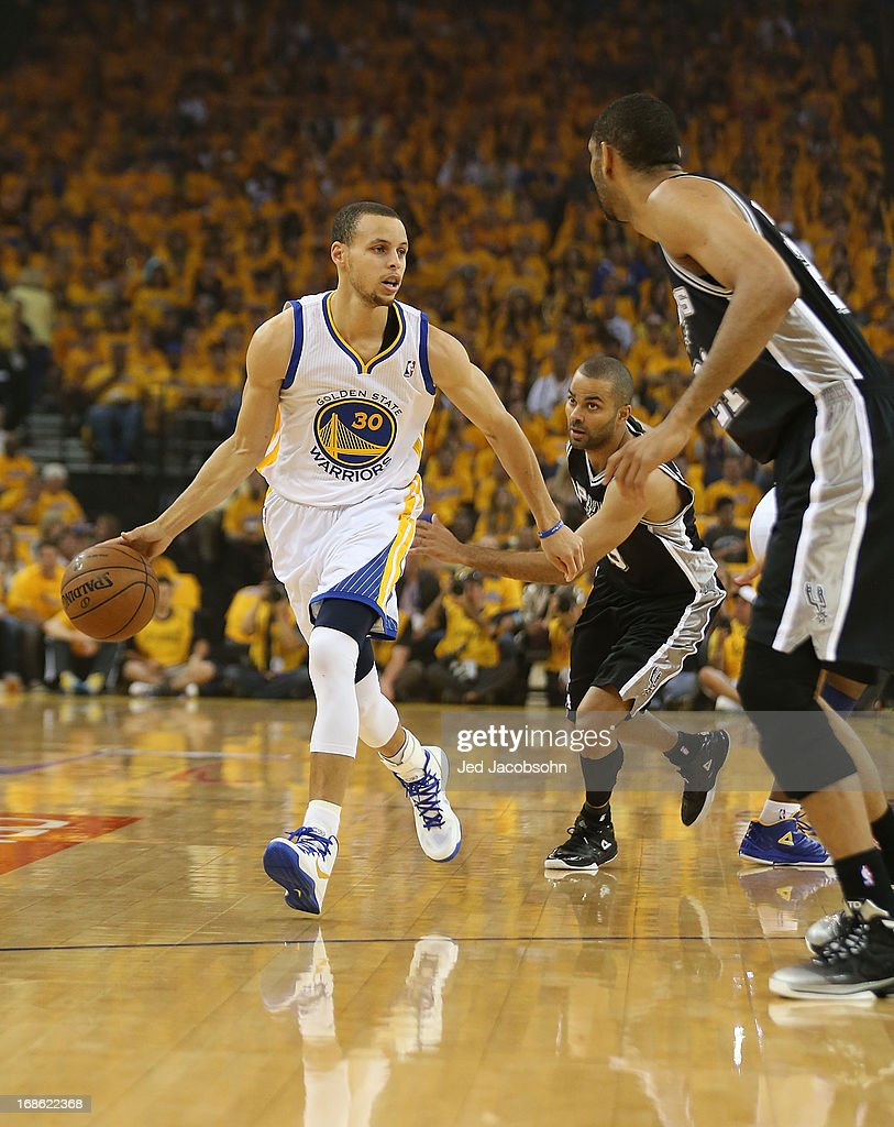 Stephen Curry #30 of the Golden State Warriors drives against Tony Parker #9 and Tim Duncan #21 of the San Antonio Spurs in Game Four of the Western Conference Semifinals during the 2013 NBA Playoffs on May 12, 2013 at the Oracle Arena in Oakland, California.