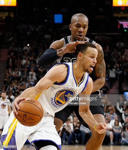 Stephen Curry of the Golden State Warriors drives in front of David West of the San Antonio Spurs at ATT Center on April 10 2016 in San Antonio Texas...