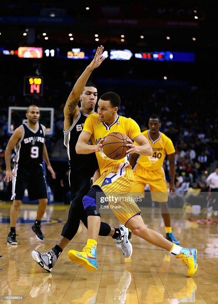 Stephen Curry #30 of the Golden State Warriors drives on Danny Green #4 of the San Antonio Spurs at Oracle Arena on February 22, 2013 in Oakland, California. The Warriors are wearing new short-sleeved uniforms for the first time.