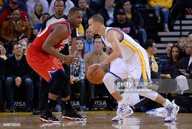Stephen Curry of the Golden State Warriors drives on Lavoy Allen of the Philadelphia 76ers at ORACLE Arena on February 10 2014 in Oakland California...