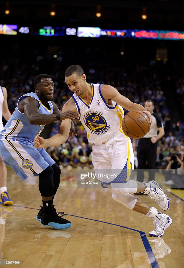 Stephen Curry #30 of the Golden State Warriors drives on Nate Robinson #10 of the Denver Nuggets at ORACLE Arena on January 15, 2014 in Oakland, California.