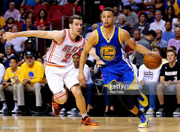 Stephen Curry of the Golden State Warriors drives past Goran Dragic of the Miami Heat during the game at the American Airlines Arena on February 24...