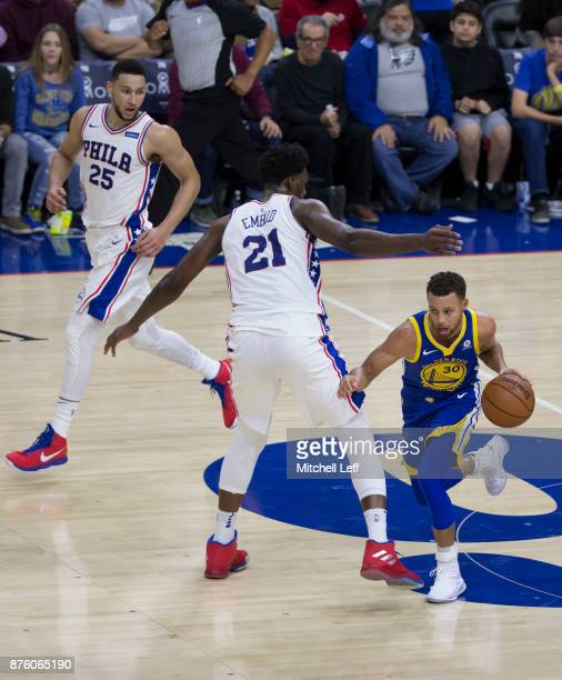 Stephen Curry of the Golden State Warriors drives to the basket against Ben Simmons and Joel Embiid of the Philadelphia 76ers in the second quarter...