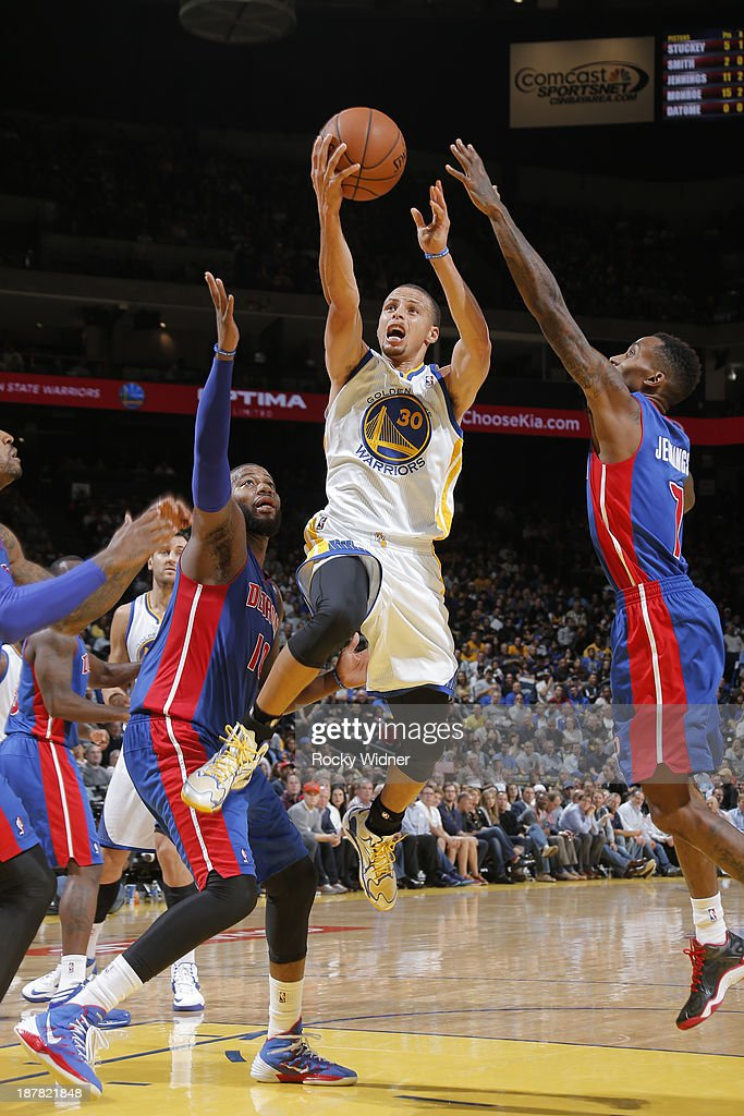 Stephen Curry #30 of the Golden State Warriors drives to the basket against <a gi-track='captionPersonalityLinkClicked' href=/galleries/search?phrase=Greg+Monroe&family=editorial&specificpeople=5042440 ng-click='$event.stopPropagation()'>Greg Monroe</a> #10 and Brandon Jennings #7 of the Detroit Pistons on November 12, 2013 at Oracle Arena in Oakland, California.