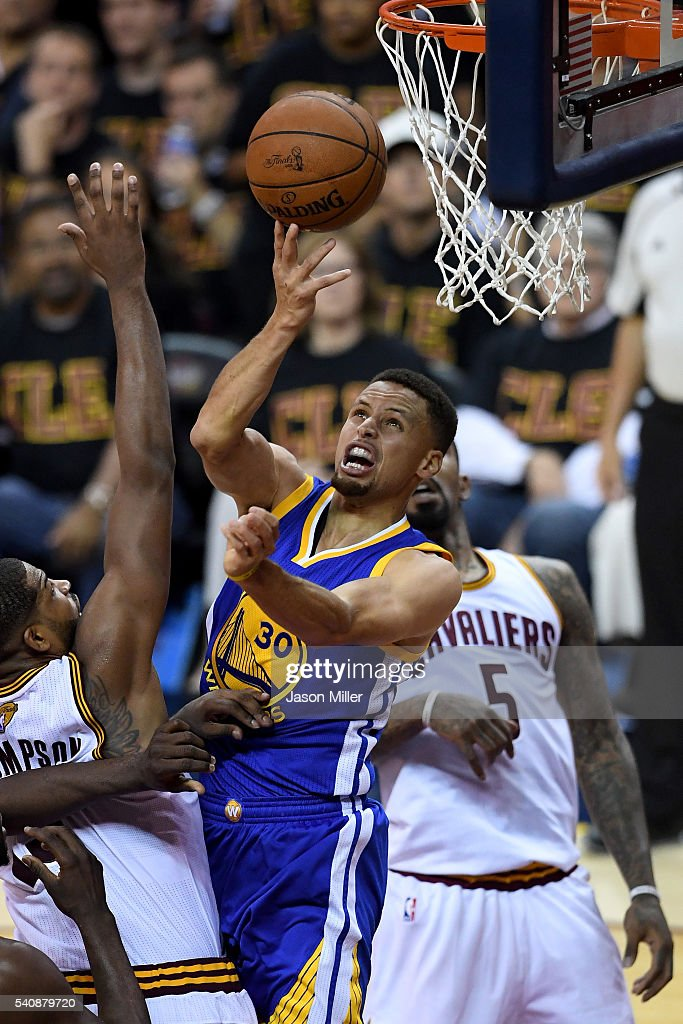 Stephen Curry of the Golden State Warriors drives to the basket against Iman Shumpert and JR Smith of the Cleveland Cavaliers in the second half in...
