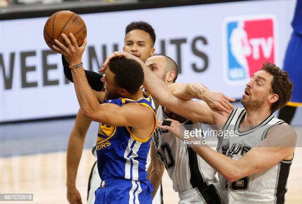 Stephen Curry of the Golden State Warriors drives to the basket against Manu Ginobili and Pau Gasol of the San Antonio Spurs in the second half...