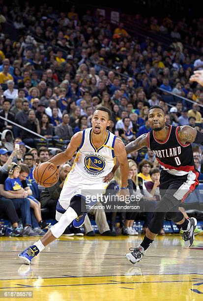 Stephen Curry of the Golden State Warriors drives to the basket past Damian Lillard of the Portland Trail Blazers during an NBA basketball game at...