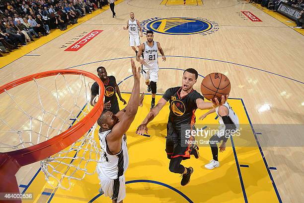 Stephen Curry of the Golden State Warriors drives to the basket against the San Antonio Spurs on February 20 2015 at Oracle Arena in Oakland...