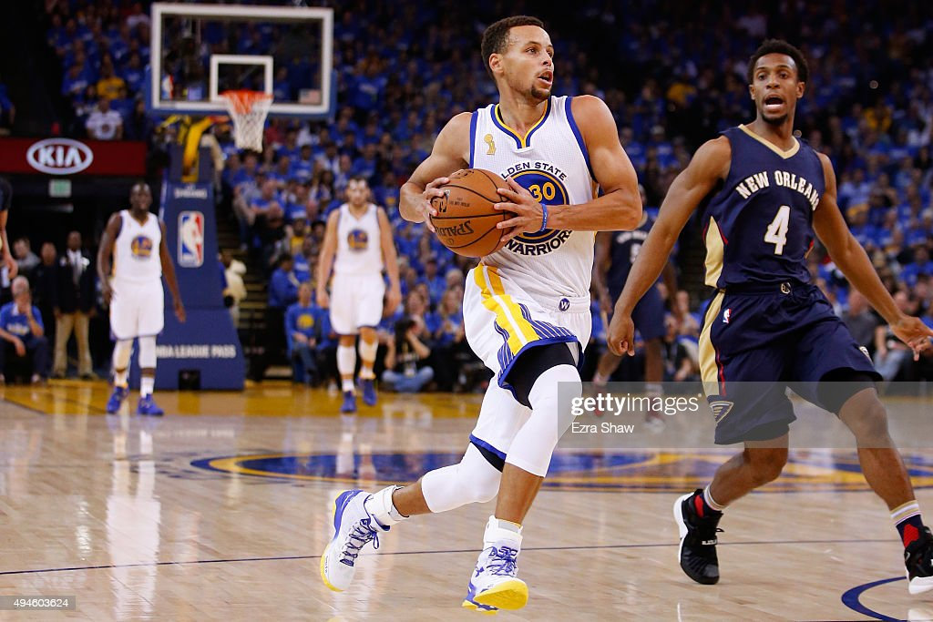 Stephen Curry of the Golden State Warriors drives to the hoop against Ish Smith of the New Orleans Pelicans during the NBA season opener at ORACLE...