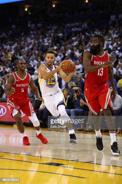 Stephen Curry of the Golden State Warriors drives with the ball against Chris Paul and James Harden of the Houston Rockets during their NBA game at...