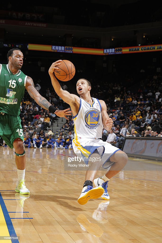 Stephen Curry #30 of the Golden State Warriors fakes a pass against <a gi-track='captionPersonalityLinkClicked' href=/galleries/search?phrase=James+Thomas+-+Basketball+Player&family=editorial&specificpeople=11519617 ng-click='$event.stopPropagation()'>James Thomas</a> #15 of the Maccabi Haifa on October 11, 2012 at Oracle Arena in Oakland, California.