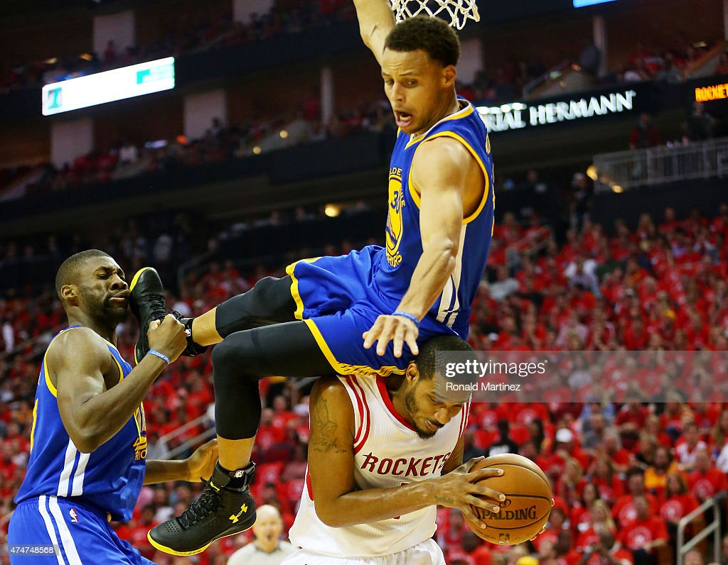 Stephen Curry #30 of the Golden State Warriors falls over Trevor Ariza #1 of the Houston Rockets on his way to an injury in the second quarter during Game Four of the Western Conference Finals of the 2015 NBA Playoffs at Toyota Center on May 25, 2015 in Houston, Texas.