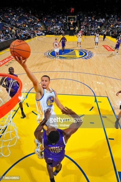 Stephen Curry of the Golden State Warriors flips up a shot over Ish Smith of the Sacramento Kings during a preseason game on December 17 2011 at...