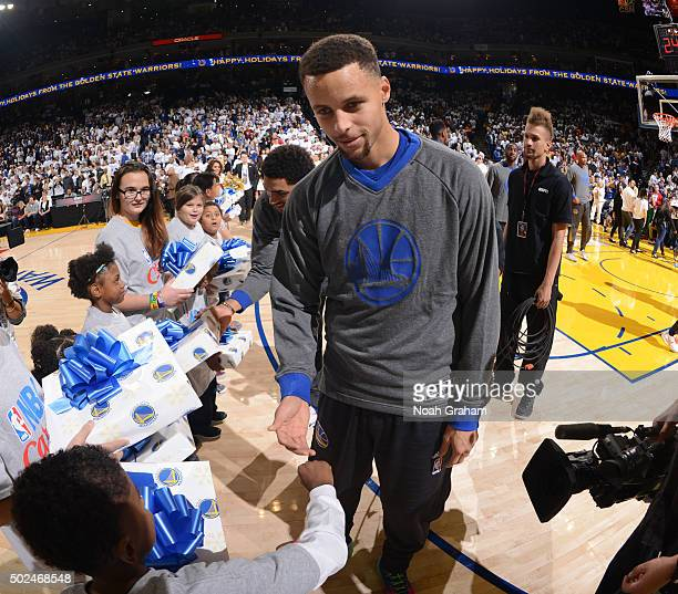 Stephen Curry of the Golden State Warriors gives gifts to children prior to the game against the Cleveland Cavaliers on December 25 2015 at ORACLE...