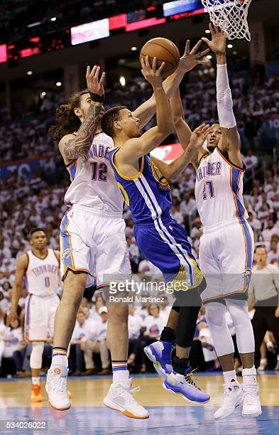Stephen Curry of the Golden State Warriors goes up against Steven Adams and Andre Roberson of the Oklahoma City Thunder in the first quater in game...