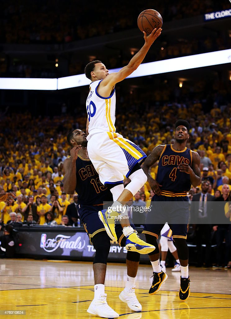 Stephen Curry #30 of the Golden State Warriors goes up against Tristan Thompson #13 and Iman Shumpert #4 of the Cleveland Cavaliers to tie the game in the final seconds of the fourth quarter during Game Two of the 2015 NBA Finals at ORACLE Arena on June 7, 2015 in Oakland, California.