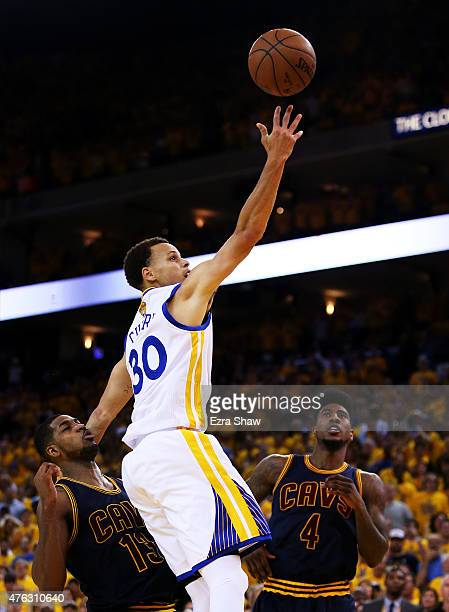 Stephen Curry of the Golden State Warriors goes up against Tristan Thompson and Iman Shumpert of the Cleveland Cavaliers to tie the game in the final...