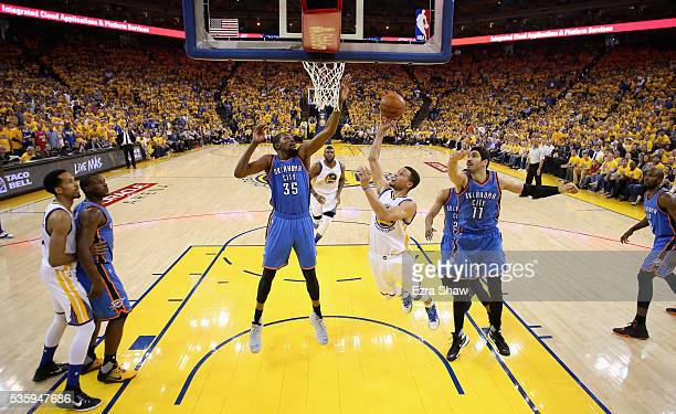Stephen Curry of the Golden State Warriors goes up for a shot against Enes Kanter and Kevin Durant of the Oklahoma City Thunder of the Oklahoma City...