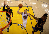 Stephen Curry of the Golden State Warriors goes up for a shot between LeBron James and Iman Shumpert of the Cleveland Cavaliers in the first half in...