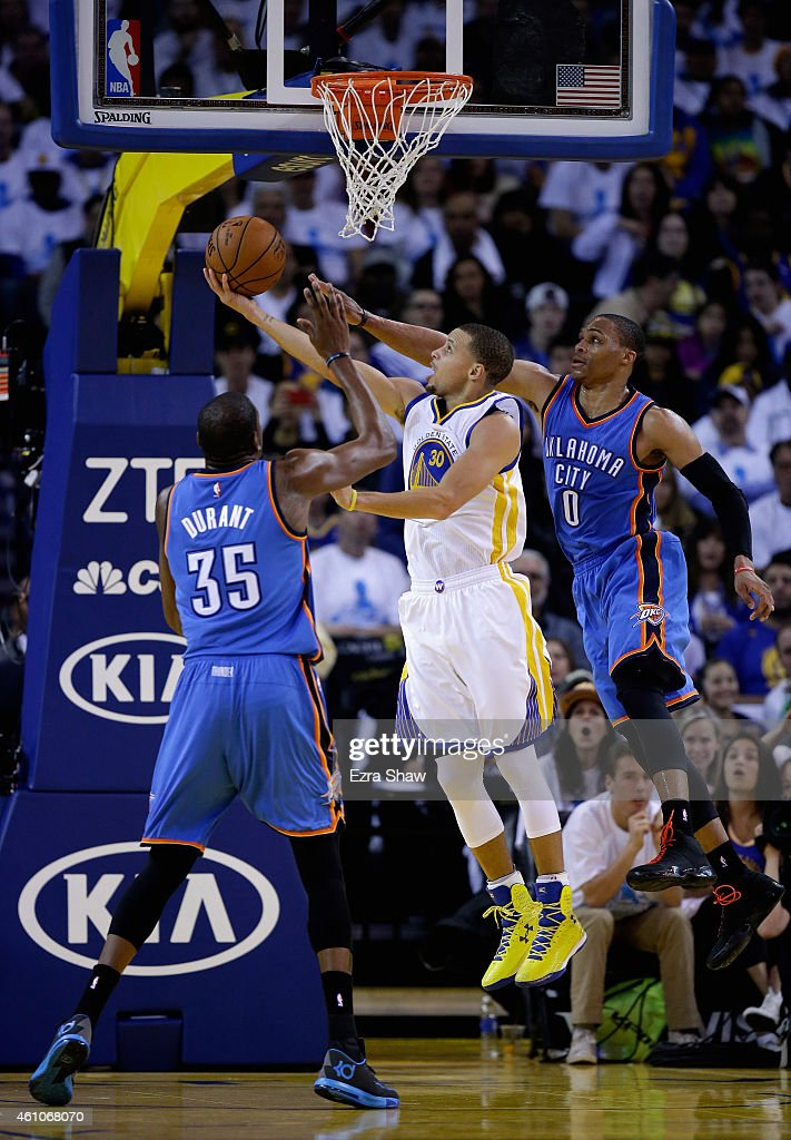 Stephen Curry of the Golden State Warriors goes up for a shot on Russell Westbrook and Kevin Durant of the Oklahoma City Thunder at ORACLE Arena on...