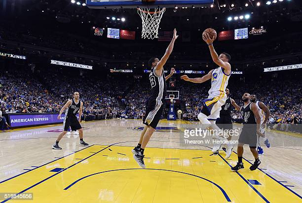 Stephen Curry of the Golden State Warriors goes up for layup over Kevin Martin of the San Antonio Spurs in the third quarter of an NBA Basketball...