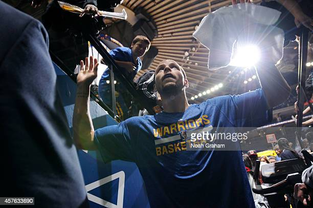 Stephen Curry of the Golden State Warriors greets fans while heading into the tunnel after defeating the Los Angeles Clippers on October 21 2014 at...