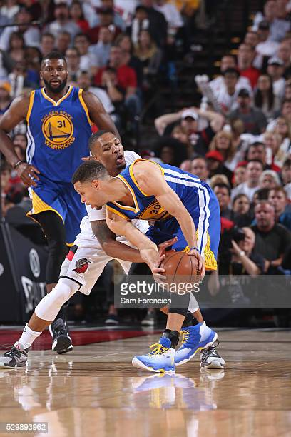 Stephen Curry of the Golden State Warriors handles the ball against Damian Lillard of the Portland Trail Blazers in Game Four of the Western...