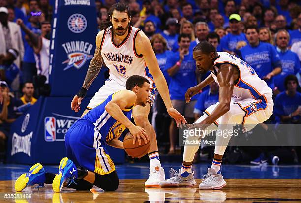 Stephen Curry of the Golden State Warriors handles the ball as Steven Adams of the Oklahoma City Thunder and Kevin Durant react during the first half...
