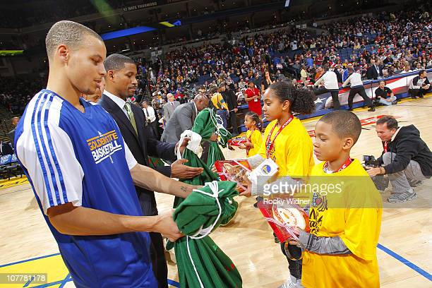Stephen Curry of the Golden State Warriors hands a lucky fan some gifts in a game against the Portland Trailblazers on December 25 2010 at Oracle...