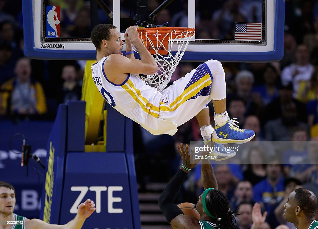Stephen Curry #30 of the Golden State Warriors hangs on the rim after dunking the ball on Gerald Wallace #45 of the Boston Celtics at ORACLE Arena on January 25, 2015 in Oakland, California.