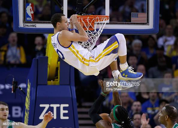 Stephen Curry of the Golden State Warriors hangs on the rim after dunking the ball on Gerald Wallace of the Boston Celtics at ORACLE Arena on January...