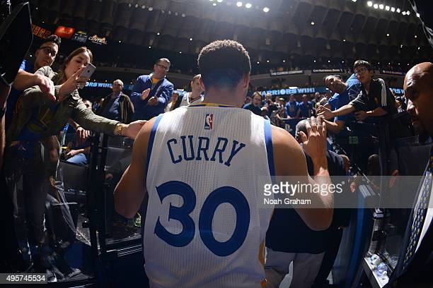 Stephen Curry of the Golden State Warriors high fives fans after defeating the Los Angeles Clippers on November 4 2015 at Oracle Arena in Oakland...