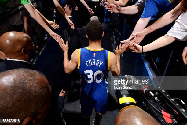 Stephen Curry of the Golden State Warriors high fives fans as he heads to the locker room after the game against the Washington Wizards on April 2...