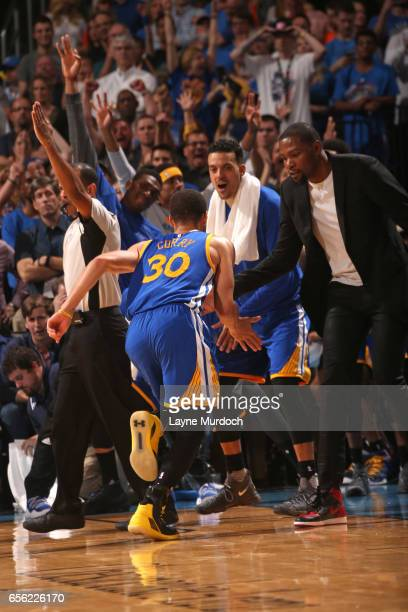 Stephen Curry of the Golden State Warriors high fives Kevin Durant after hitting a three pointer during the game against the Oklahoma City Thunder on...