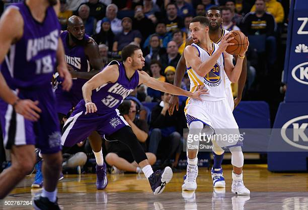 Stephen Curry of the Golden State Warriors is covered by Seth Curry of the Sacramento Kings at ORACLE Arena on December 28 2015 in Oakland California...