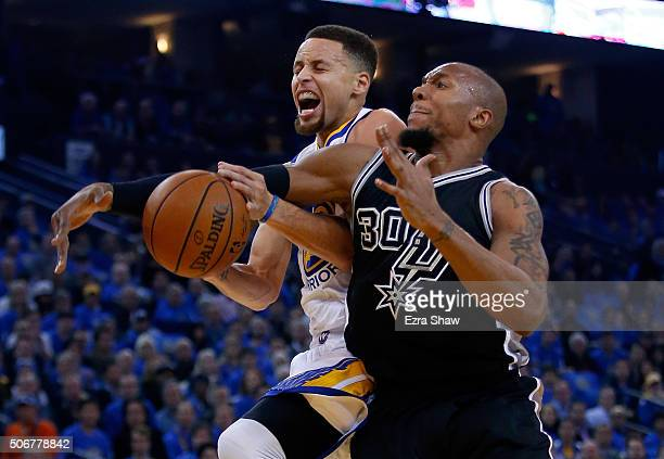 Stephen Curry of the Golden State Warriors is fouled by David West of the San Antonio Spurs at ORACLE Arena on January 25 2016 in Oakland California...