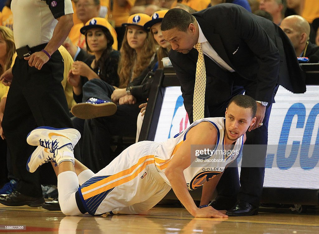 Stephen Curry #30 of the Golden State Warriors is helped up by head coach Mark Jackson against the San Antonio Spurs in Game Four of the Western Conference Semifinals during the 2013 NBA Playoffs on May 12, 2013 at the Oracle Arena in Oakland, California.