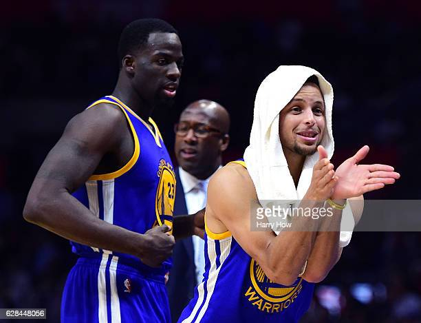 Stephen Curry of the Golden State Warriors jokes on the sidelines in front of Draymond Green and Mike Brown during a 11598 Warriors win over the LA...