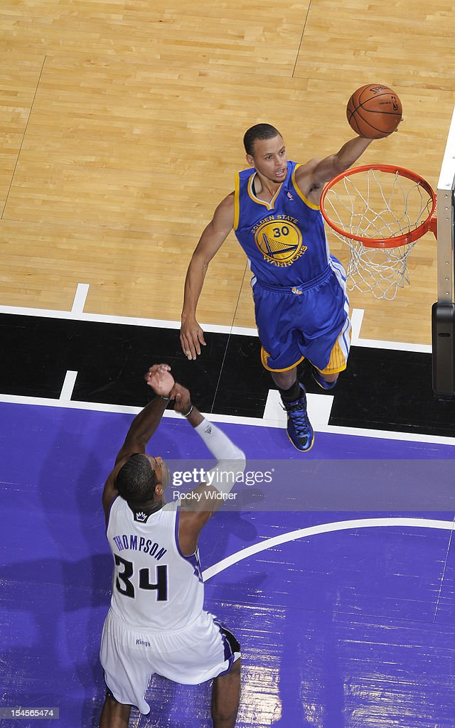 Stephen Curry #30 of the Golden State Warriors lays the ball in against Jason Thompson #34 of the Sacramento Kings on October 17, 2012 at Power Balance Pavilion in Sacramento, California.