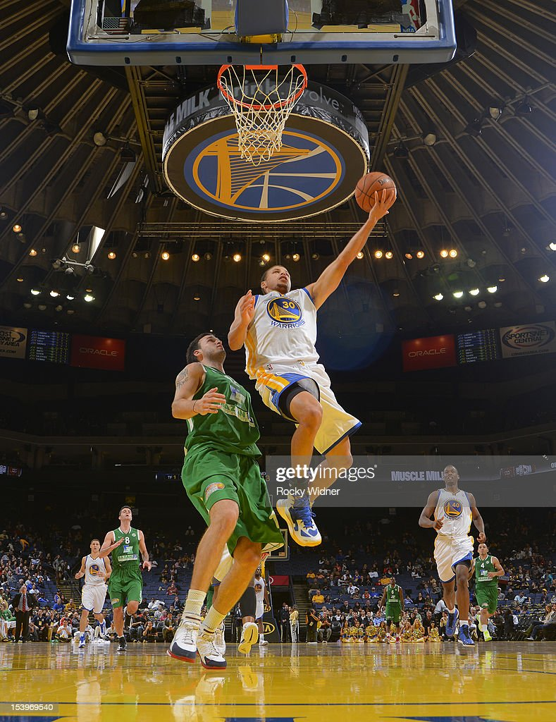 Stephen Curry #30 of the Golden State Warriors lays the ball up against Pat Calathes #12 of the Maccabi Haifa on October 11, 2012 at Oracle Arena in Oakland, California.