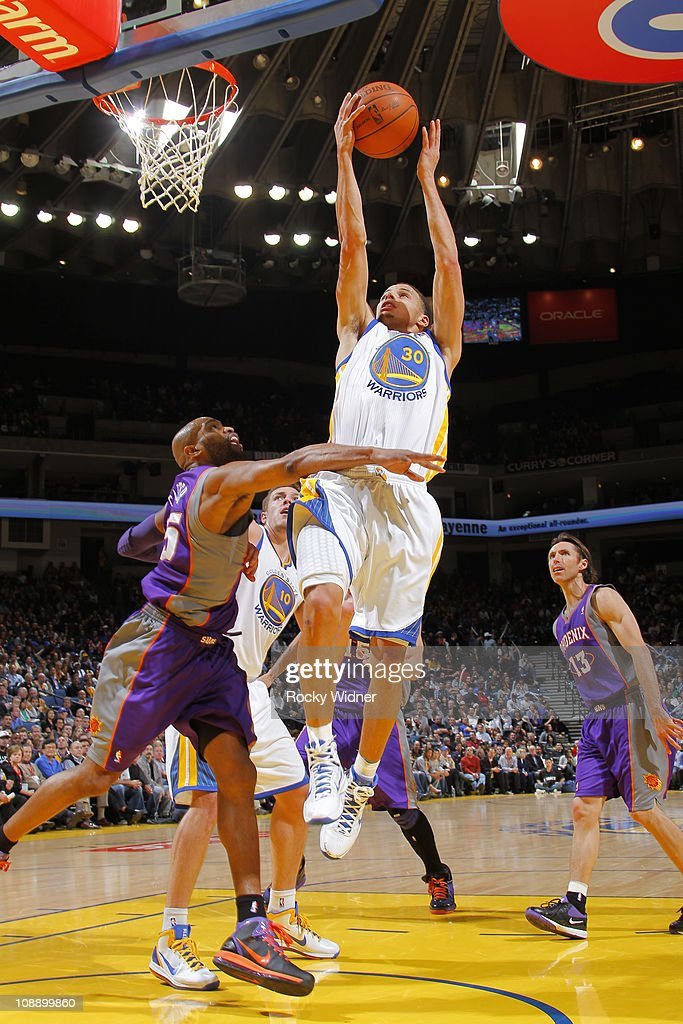 Stephen Curry #30 of the Golden State Warriors lays the ball up over <a gi-track='captionPersonalityLinkClicked' href=/galleries/search?phrase=Vince+Carter&family=editorial&specificpeople=201488 ng-click='$event.stopPropagation()'>Vince Carter</a> #15 of the Phoenix Suns on February 7, 2011 at Oracle Arena in Oakland, California.