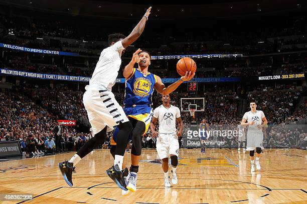 Stephen Curry of the Golden State Warriors lays up a shot against Emmanuel Mudiay of the Denver Nuggets at Pepsi Center on November 22 2015 in Denver...