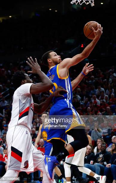 Stephen Curry of the Golden State Warriors lays up the ball over Al Farouq Aminu of the Portland Trail Blazers during Game Three of the Western...
