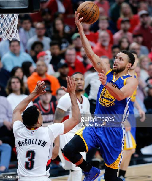 Stephen Curry of the Golden State Warriors lays up the ball over CJ McCollum the Portland Trail Blazers during Game Three of the Western Conference...