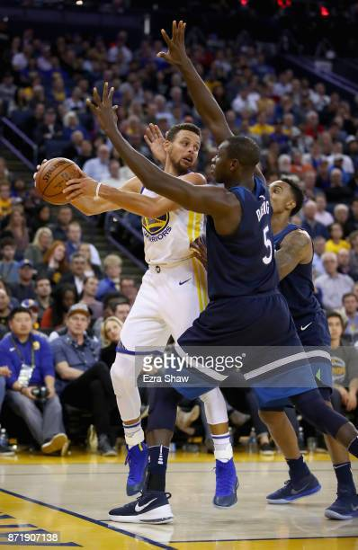 Stephen Curry of the Golden State Warriors looks to pass around Gorgui Dieng of the Minnesota Timberwolves at ORACLE Arena on November 8 2017 in...